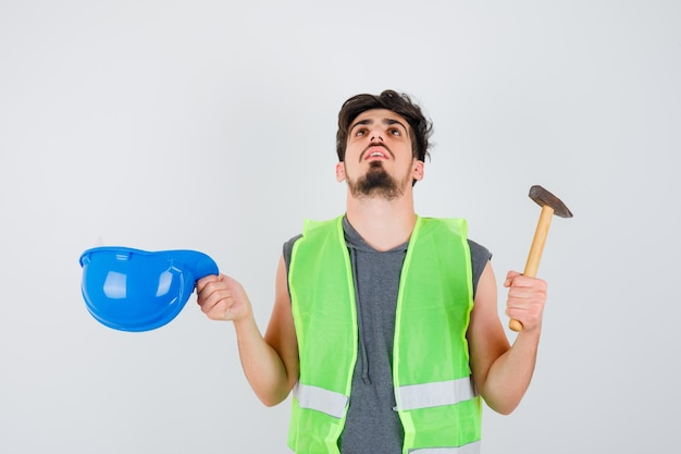Молодой рабочий в строительной форме держит топор в одной руке, снимает кепку и выглядит озадаченным