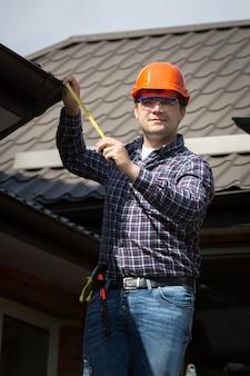 집 지붕의 크기를 측정하는 하드 모자에 젊은 노동자