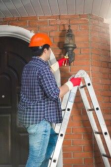 家で屋外ランプを修理するヘルメットの若い労働者