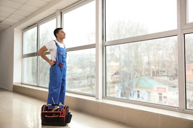 大きな窓のある部屋の若い労働者