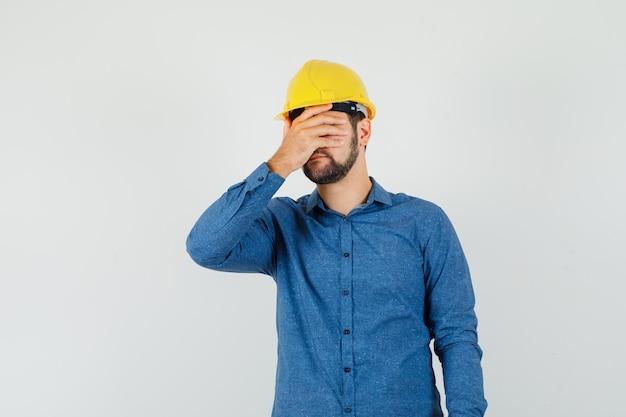シャツを着た若い労働者、目に手をつないで、苦しんでいるように見えるヘルメット