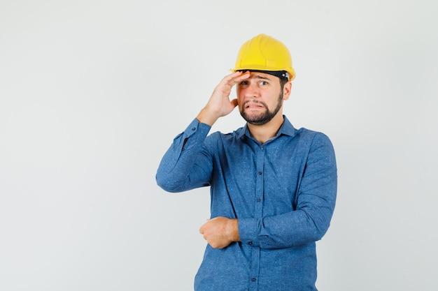 シャツを着た若い労働者、顔に手をかざし、恥ずかしそうに見えるヘルメット