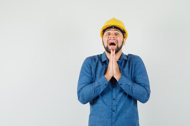 셔츠에 젊은 노동자, 헬멧은 제스처를기도하고 낙관적 찾고 손을 잡고