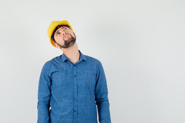 シャツを着た若い労働者、上向きで思慮深いヘルメット