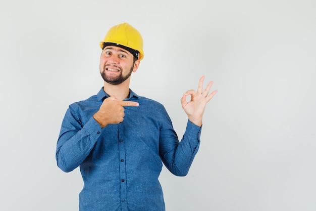 셔츠에 젊은 노동자, 헬멧 그의 확인 기호를 가리키고 쾌활한 찾고