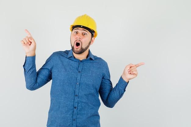 셔츠에 젊은 노동자, 헬멧 멀리 가리키고 충격을 찾고