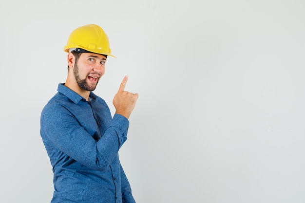 셔츠에 젊은 노동자, 헬멧 가리키는 손가락과 기분 좋은 찾고