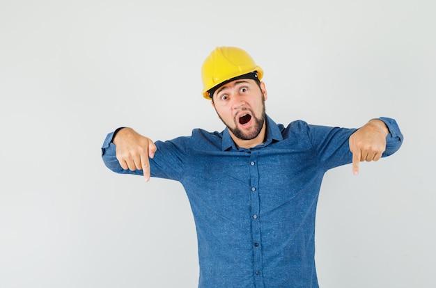 シャツを着た若い労働者、ヘルメットが指を下に向けて驚いている