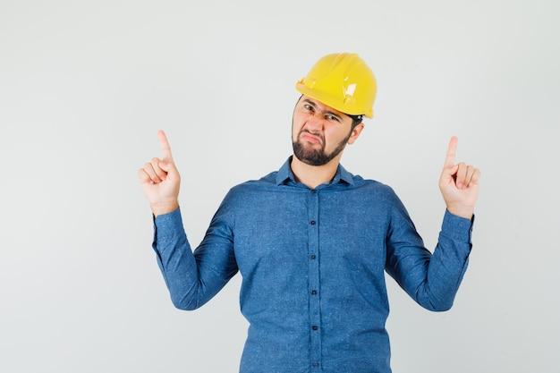 シャツを着た若い労働者、ヘルメットが指を上に向け、不満を感じている