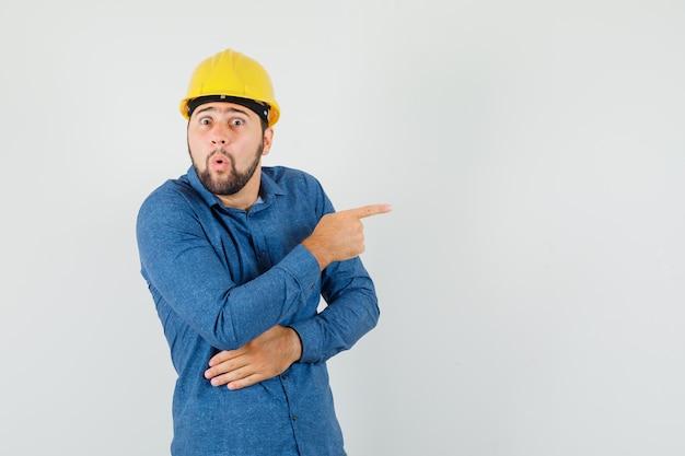 シャツを着た若い労働者、側面を指して不思議に見えるヘルメット