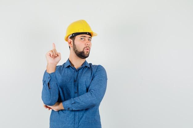シャツを着た若い労働者、ヘルメットを上向きにして好奇心旺盛に見える