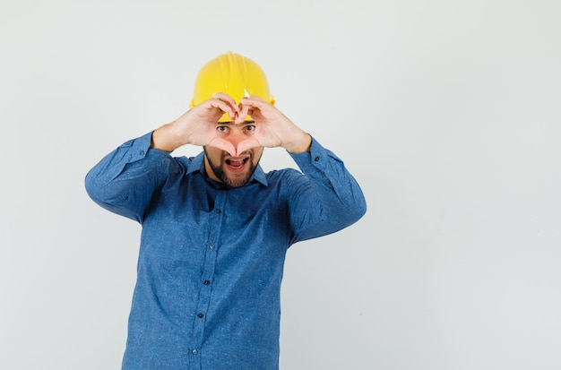 Молодой работник в рубашке, шлеме показывает жест сердца и выглядит весело