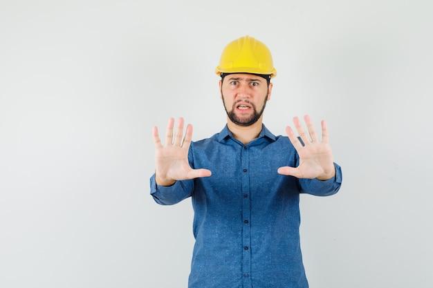 シャツを着た若い労働者、拒否のジェスチャーを示し、イライラしているように見えるヘルメット
