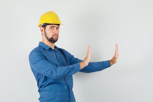 シャツを着た若い労働者、拒否のジェスチャーを示し、厳格に見えるヘルメット