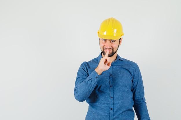 シャツを着た若い労働者、沈黙のジェスチャーを示し、注意深く見えるヘルメット