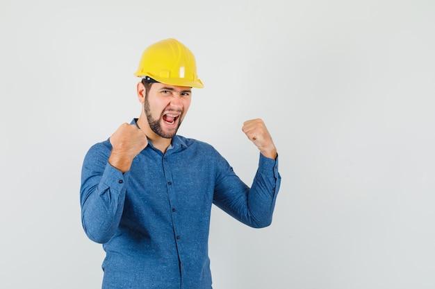 シャツを着た若い労働者、勝者のジェスチャーを示し、幸せそうに見えるヘルメット