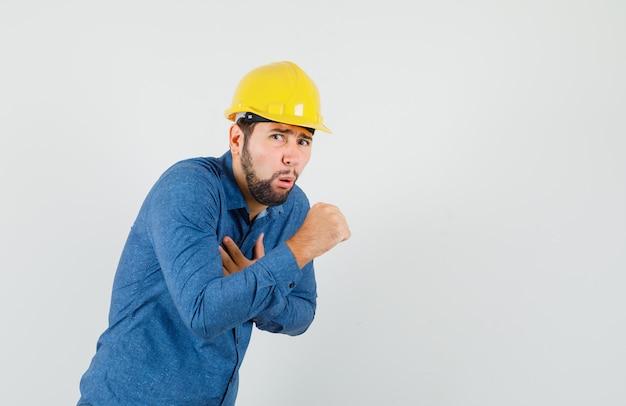 シャツを着た若い労働者、咳に苦しんでいるヘルメット、体調不良