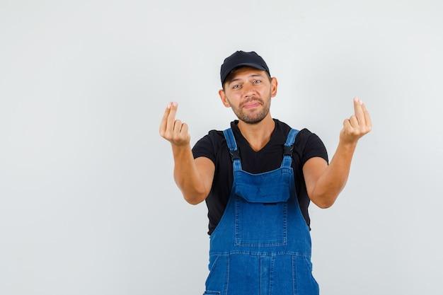指で身振りで示す均一な若い労働者と穏やかに見える、正面図。