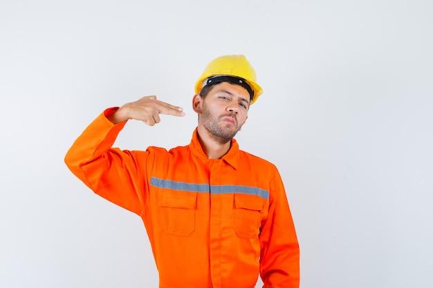 Молодой рабочий в форме жестикулирует рукой и пальцами и выглядит уверенно.