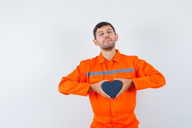 現在の箱を持って自信を持って見える制服を着た若い労働者。