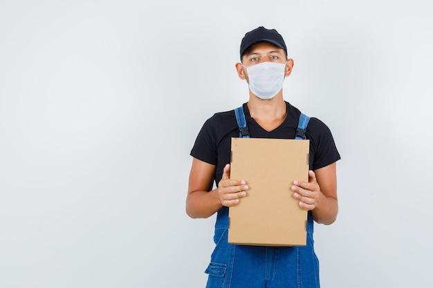 Молодой работник в форме, маска, держащая картонную коробку и серьезный вид, вид спереди.