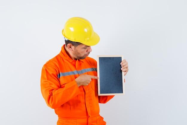 균일 한 칠판에 가리키는 찾고 초점을 맞춘 젊은 노동자.