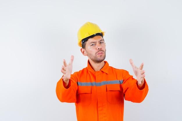 뭔가 잡기로 손을 올리는 제복을 입은 젊은 노동자.