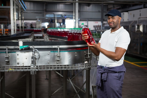 Молодой рабочий осматривает бутылку сока на заводе