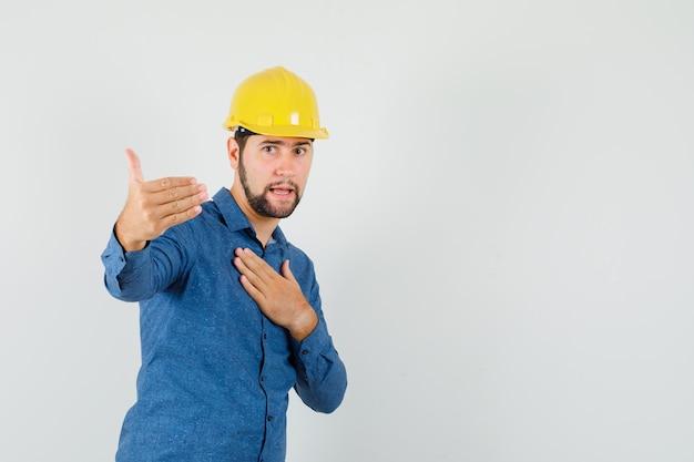Молодой рабочий приглашает приехать, держа руку на груди в рубашке, шлеме