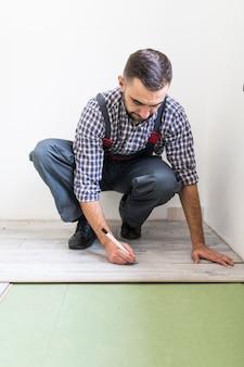 Giovane operaio che riveste un pavimento con assi del pavimento laminato