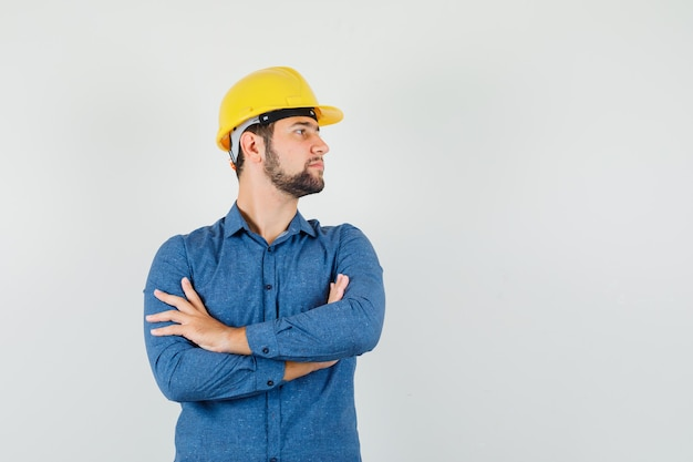 シャツ、ヘルメット、焦点を合わせて腕を組んで脇を見ている若い労働者。