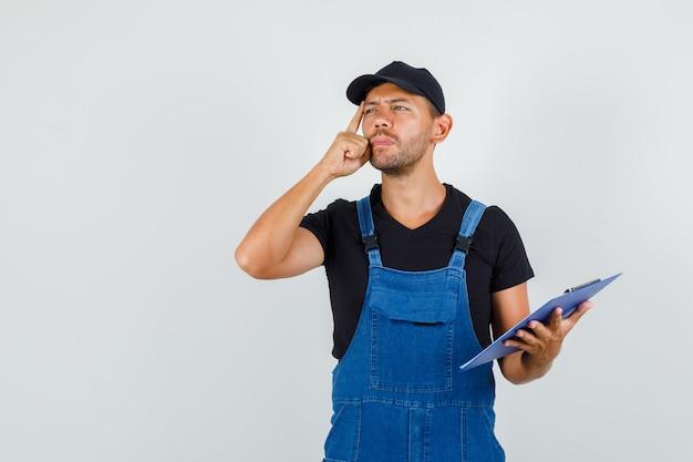 Giovane operaio distoglie lo sguardo tenendo appunti in uniforme e guardando pensieroso, vista frontale.