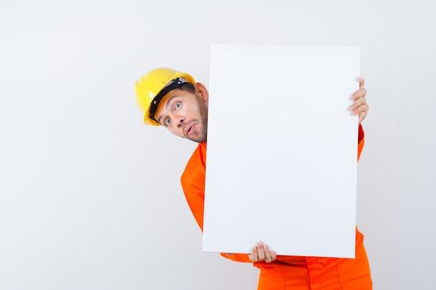 Giovane operaio guardando fuori da dietro una tela bianca in uniforme, casco.