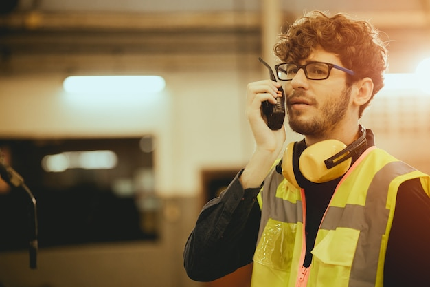 Young worker man using radio control communication in factory
