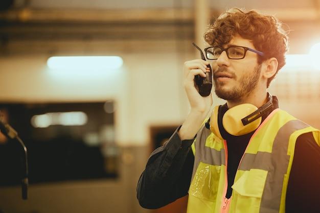 Молодой рабочий человек с помощью радиоуправления на заводе