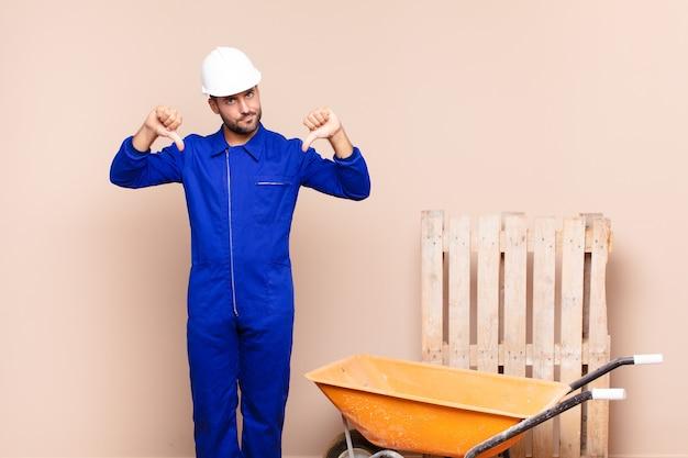 Молодой рабочий человек с тачкой