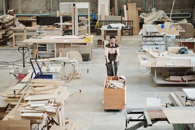 ワークショップに沿って移動しながら、ワークピースの残り物でいっぱいの大きな箱でカートを押す現代の工場の若い労働者