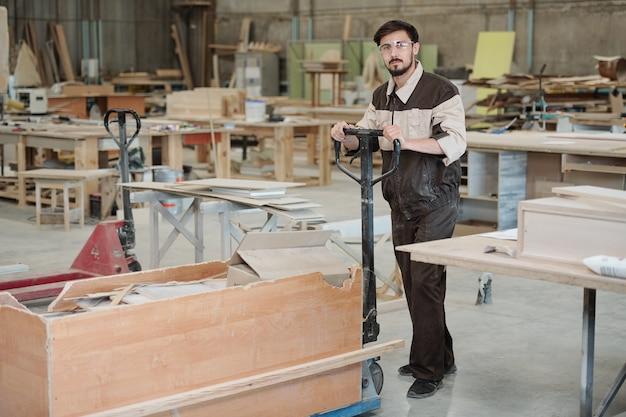 Молодой рабочий современной фабрики толкает тележку с большой коробкой, полной остатков заготовок, двигаясь по цеху