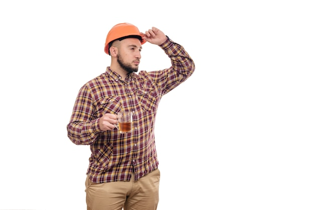 Young worker in an orange helmet holds a cup of tea, isolated white background