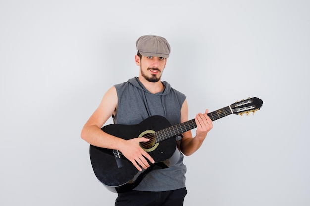 Young worker playing guitar in gray t-shirt and cap and looking happy