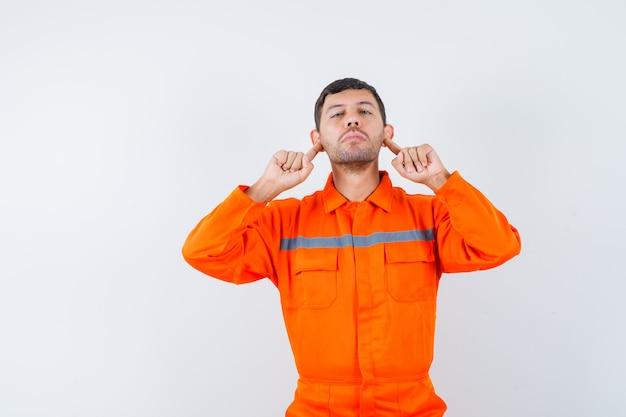 Молодой рабочий, указывая на мочки ушей в униформе.