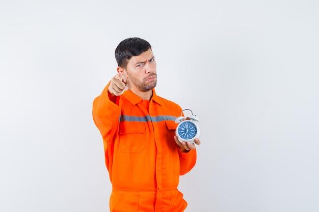 Молодой работник указывая на фронт, держа будильник в униформе и серьезный взгляд.