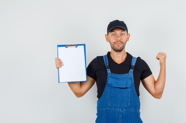 Young worker pointing back and holding clipboard in uniform front view.