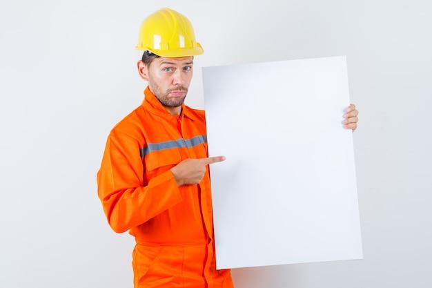 Giovane operaio che punta alla tela bianca in uniforme, casco.