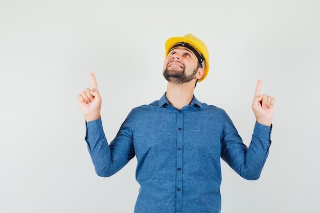 シャツ、ヘルメット、感謝の気持ちで指を上に向ける若い労働者