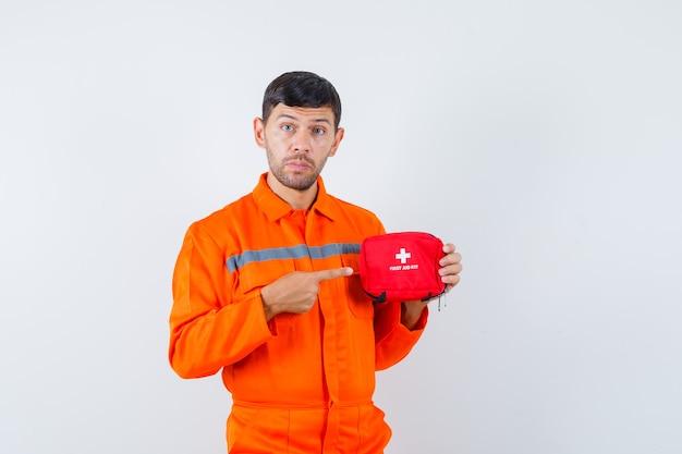 Giovane operaio che indica al kit di pronto soccorso in uniforme e che osserva attento.