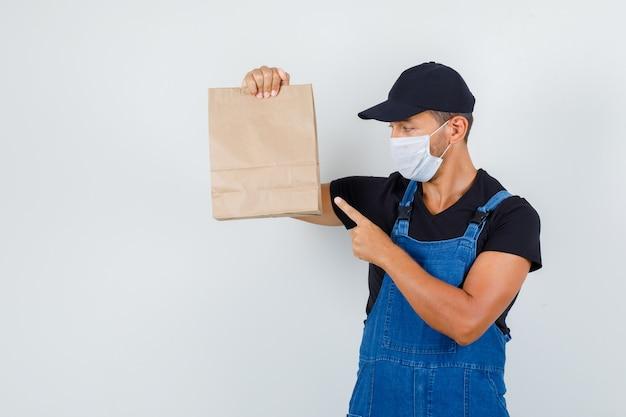 Giovane operaio che indica al sacchetto di carta in uniforme, maschera, vista frontale.