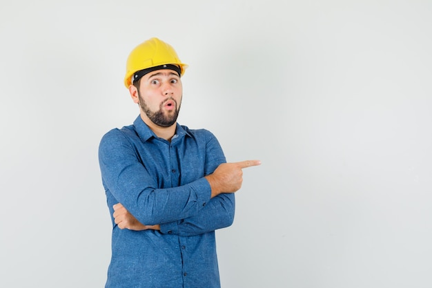 Young worker pointing to the side in shirt, helmet and looking surprised.