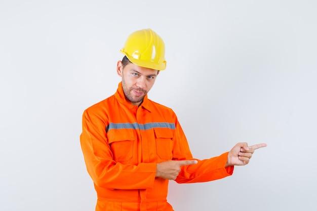 Молодой рабочий, указывая в сторону и улыбаясь в форме, шлем.