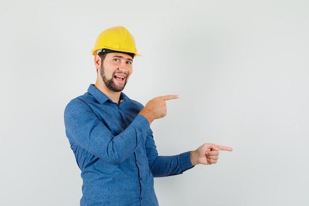 Молодой рабочий, указывая в сторону в рубашке, шлеме и выглядит веселым.